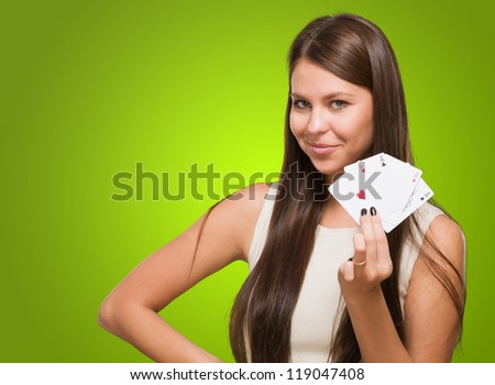 Young Woman Holding Playing Cards against a green background - stock photo