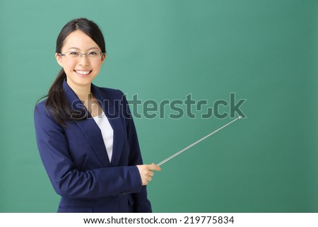 young woman holding pointer against green background - stock photo