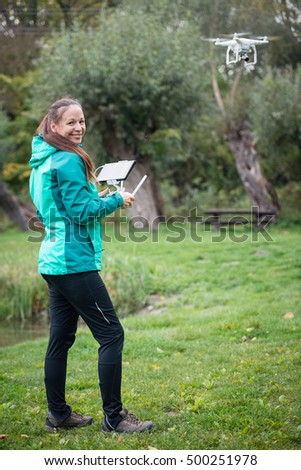 Young woman holding radio controller and flying a drone in a nature