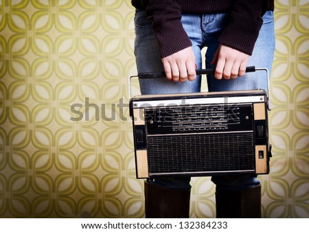young woman holding radio player in room with vintage wallpaper, detail, retro stylization 60-70s, toned