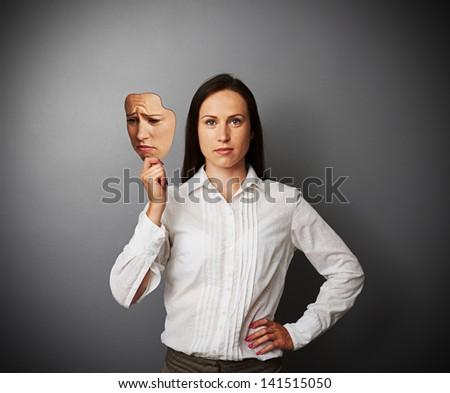 young woman holding sad mask - stock photo
