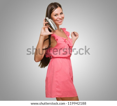 Young Woman Holding Shaker against a grey background - stock photo