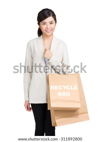 Young woman holding shopping bag and showing recycle bag