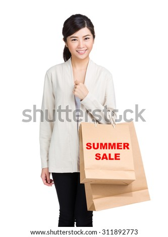 Young woman holding shopping bag and showing summer sale