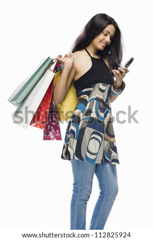 Young woman holding shopping bags and a mobile phone - stock photo
