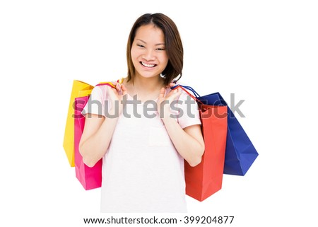 Young woman holding shopping bags and smiling on white background