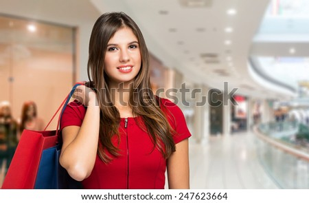 Young woman holding shopping bags in a shopping mall - stock photo