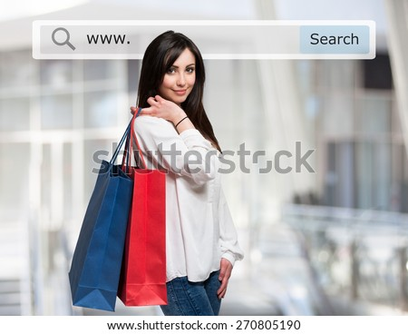 Young woman holding shopping bags in front of a search bar. Ecommerce concept - stock photo
