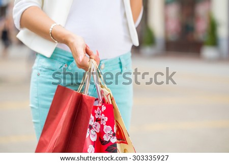 young woman holding shopping bags on street