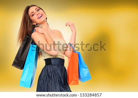 young woman holding shopping bags over abstract yellow background