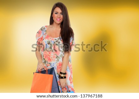 young woman holding shopping bags over abstract yellow background - stock photo