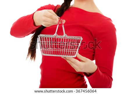 Young woman holding small empty shopping cart - stock photo