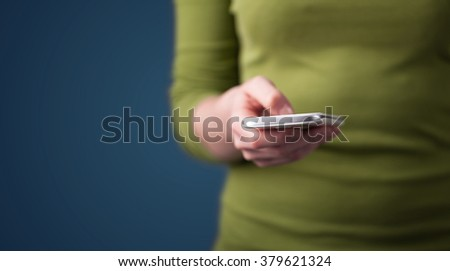 Young woman holding smarthphone in hand while typing - stock photo