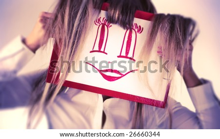 Young woman holding smiling face picture. Soft blue and yellow colors. - stock photo