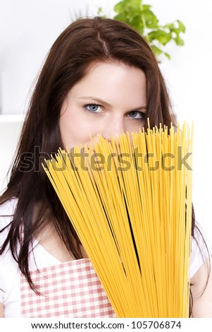 young woman holding  spaghetti to her face - stock photo