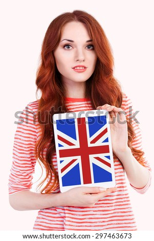Young woman holding tablet PC with a British national flag on screen. Separated on white background. English language learning concept