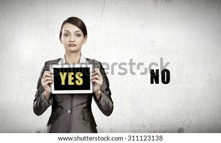 Young woman holding tablet pc with word yes - stock photo