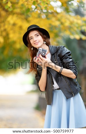 Young woman holding the camera outdoors. Beautiful hipster girl shooting with retro camera. In the autumn sunny day, beautiful girl hipster in a hat photographed on the city street