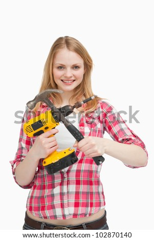 Young woman holding tools against white background - stock photo