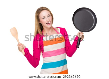 Young woman holding up with frying pan and wooden ladle - stock photo