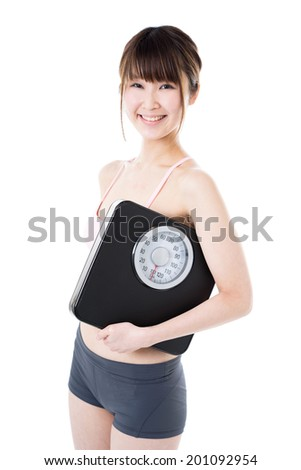 Young woman holding weighting machine isolated on white background