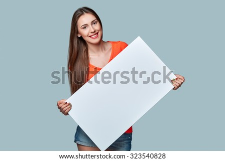 Young woman holding white blank cardboard, over gray background. - stock photo