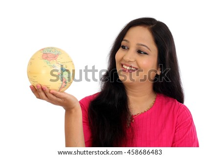 Young woman holding world globe against white background