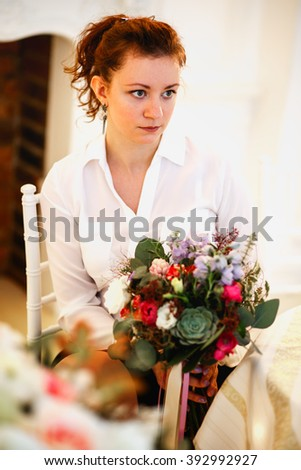 young woman holds a bouquet she made. Decor and floral composition on a table.
