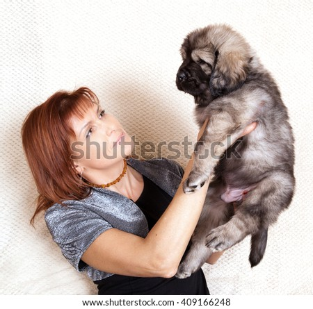 Young woman holds a gray Tibetan mastiff puppy