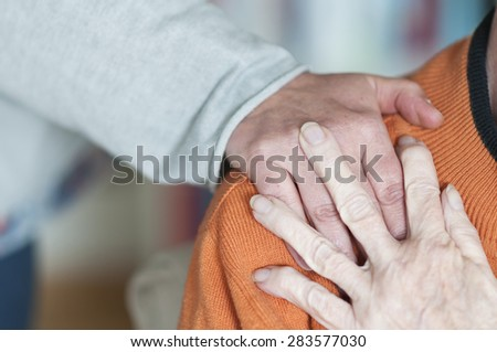 Young woman holds a hand on the shoulder of a senior citizen. - stock photo