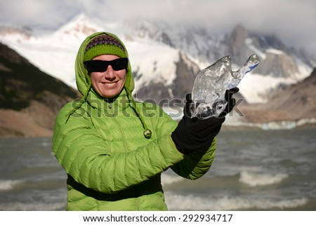 Young woman holds a piece of ice from glacier, Patagonia, Chile, South America
