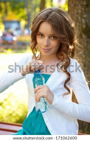 Young woman holds bottle of mineral water. - stock photo