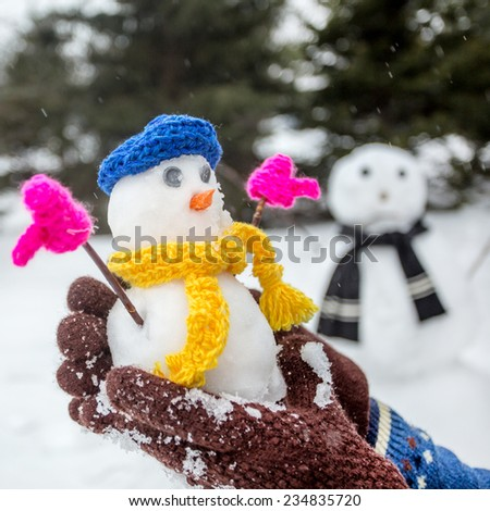 Young woman holds funny small snowman with a big snowman in the background. focus on head of snowman - stock photo