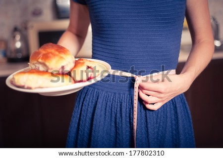 young woman holds pie and a measuring tape, care about health - stock photo