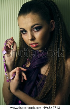 Young woman holds violet necklace in her arms