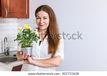 Young woman housewife stands at kitchen, holding yellow roses at pot in hands, copy space - stock photo