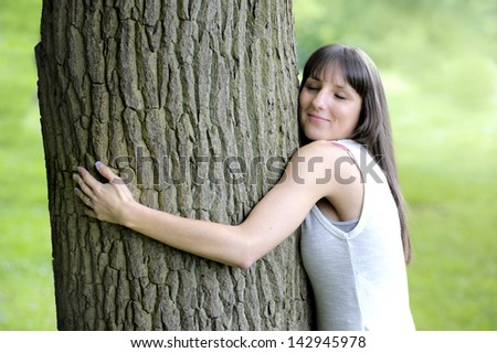 young woman hugging a big tree - stock photo