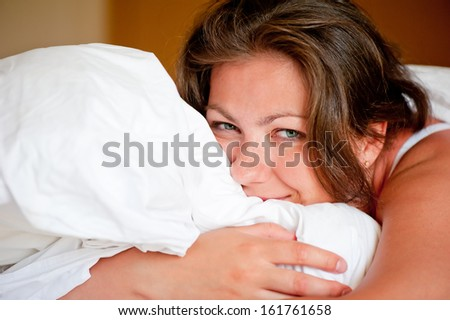 young woman hugging a pillow in bed