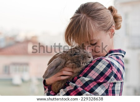 Young woman hugs big cute rabbit friend pet in her hands on city background - stock photo