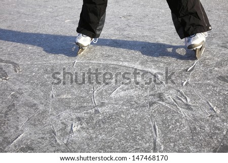 Young woman ice skating outdoors on a pond on a freezing winter day - detail of the legs - stock photo