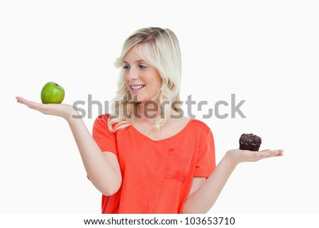 Young woman imitating a balance to choose between a fruit and chocolate - stock photo