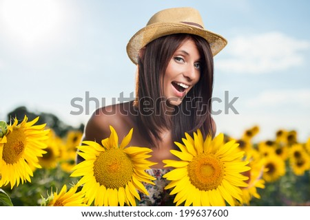 Young woman imitating her breast with two sunflowers in a field - stock photo