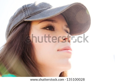 Young woman in a baseball cap portrait - stock photo