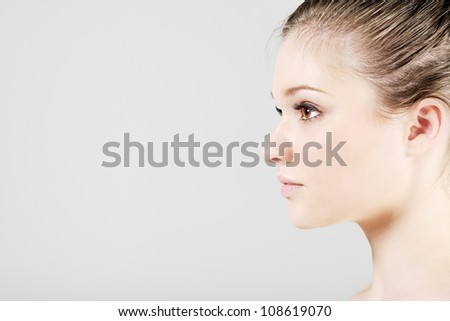 Young woman in a beauty style pose in profile - stock photo