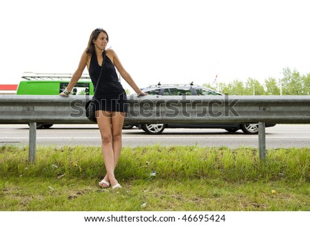 Young woman in a black mini dress leaning on the safety barrier alongside a highway - stock photo