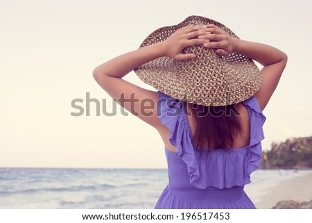 Young woman in a blue dress and a straw hat walking on the coral beach