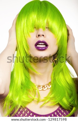 young woman in a bright green wig, indoor - stock photo