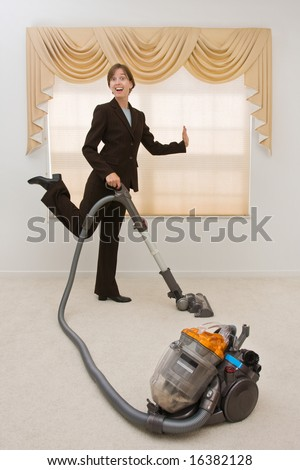 Young woman in a business suit vacuuming in an exaggerated pose. Selective focus on the vacuum. - stock photo