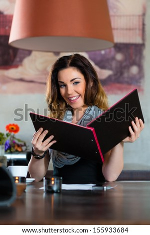 Young woman in a cafe or restaurant, looking in the menu card and choose - stock photo
