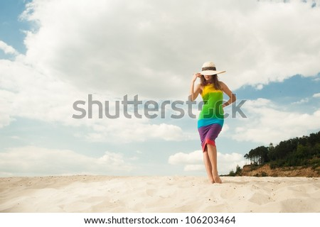 Young woman in a colorful dress on sky background - stock photo
